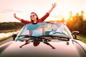 happy couple in car on vacation