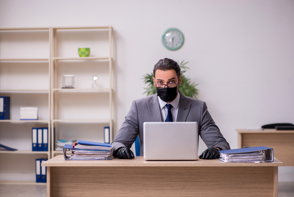 man at desk with mask